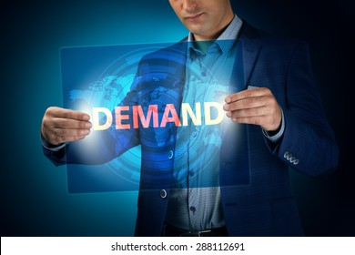 Businessman holding a transparent screen with an inscription a demand. Business, technology, internet and networking concept.
