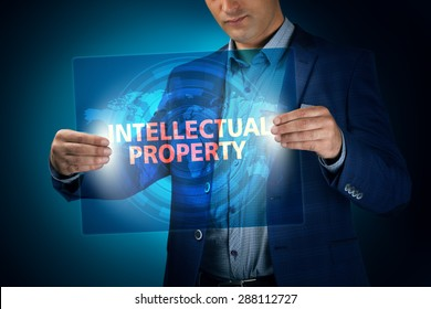 Businessman holding a transparent screen with an inscription a intellectual property. Business, technology, internet and networking concept.