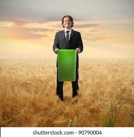 Businessman holding a trash bin on a wheat field