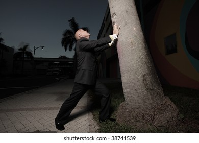Businessman holding up a tree from falling