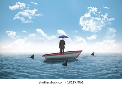 Businessman holding umbrella against sharks circling small boat in the ocean