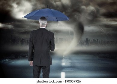 Businessman holding umbrella against stormy sky with tornado over road