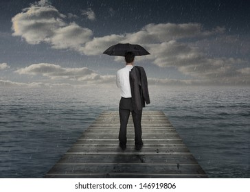 Businessman holding an umbrella and his jacket over his shoulder