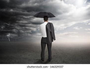 Businessman holding an umbrella and a jacket over his shoulder facing a storm