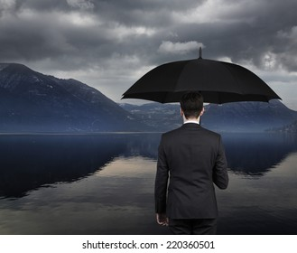 Businessman holding an umbrella and looking at lake and mountain,