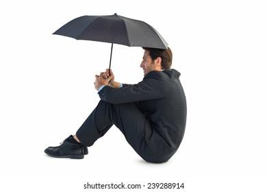 Businessman holding umbrella sitting on the floor on white background