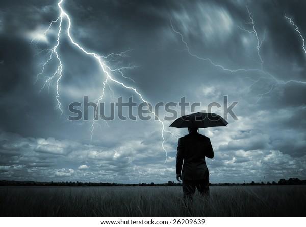 Ein Geschäftsmann, der einen Regenschirm im Sturm hält.