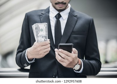 Businessman holding US Dollar bills while using smartphone for online banking. e-commerce and investment concept.