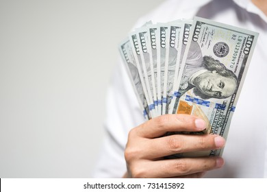 Businessman holding US dollar money in hand on white background. USD bills in concept of investment, financial and successful in business.