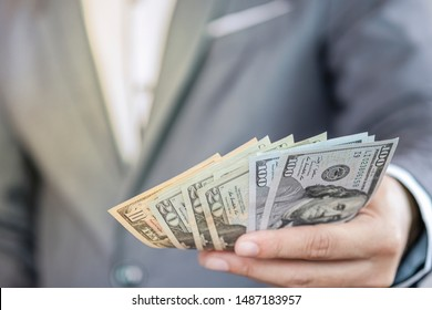 Businessman holding USD banknote for payment .US dollar is main and popular currency of exchange in the world. Investment and saving concept.