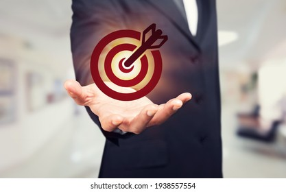 Businessman holding virtual dartboard with an arrow, target concept. - Shutterstock ID 1938557554