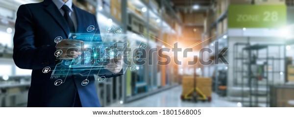 Businessman holding virtual interface panel of global logistics network distribution and transportation, Smart logistics, Innovation future of transport on large warehouse center background.