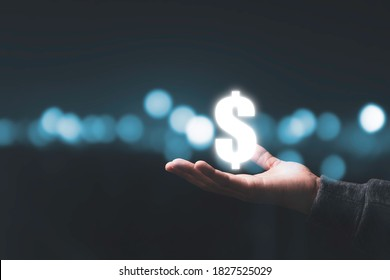 Businessman holding virtual US dollar sign with beautiful bokeh background. USD is main exchange currency in the world.