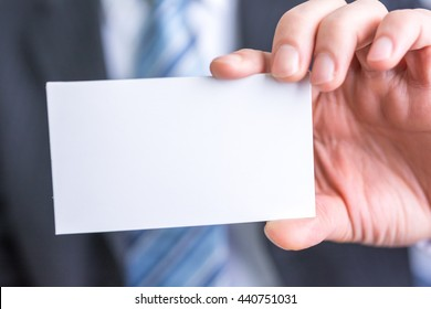 businessman holding white blank paper