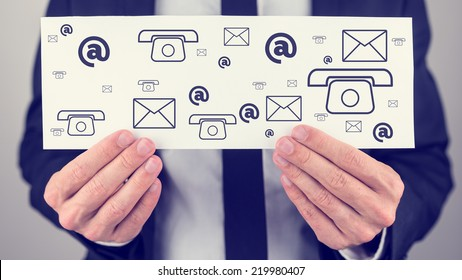 Businessman holding a white card or sign with a variety of different contact icons for mail, email, web and telephone in a communication concept.