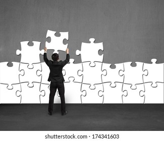 Businessman holding white puzzle to assembly on concrete wall