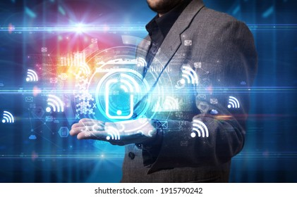 Businessman holding wifi signal icon in his hands with multiple technology symbols around it