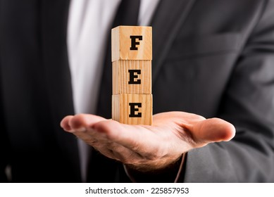 Businessman holding wooden alphabet blocks reading - Fee - balanced in the palm of his hand.