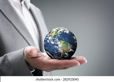 Businessman holding the world in the palm of hands concept for global business, communications, politics or environmental conservation  Earth image courtesy of Nasa