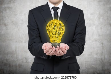 Businessman is holding an yellow light bulb. A concept of starting up of a new business project.