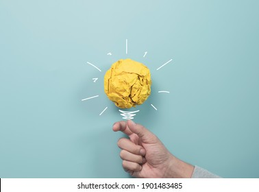 Businessman holding yellow scrap paper ball with illustration painting for virtual lightbulb. It is creative thinking idea and innovation concept.