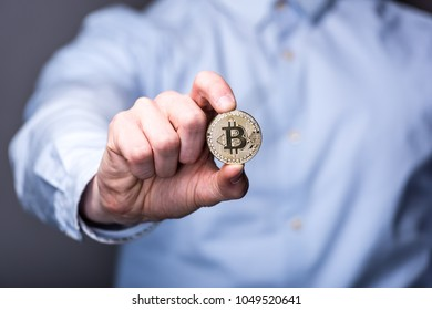 Businessman holds bitcoin in front of him with shallow depth of field