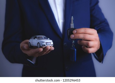 businessman holds car and keys