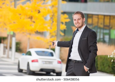 Businessman holds car keys in front of his car. Man in suit holding car keys from his white sport car.