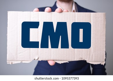 A businessman holds a cardboard with an inscription:CMO