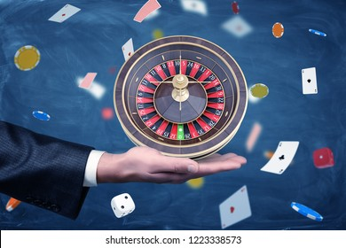 A businessman holds a casino roulette on his palm on a background of chips and cards. Business and chance. Playing your cards right. High stakes.