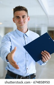 Businessman holds a clipboard in his hand stretches his palm for a handshake welcomes says hello invites you to take training and sign a contract