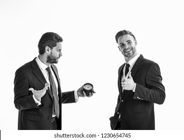 Businessman holds clock with thoughtful face and his partner with smiling face shows thumb up. Business and punctuality concept. Men in classic suits with opposite emotions stand on white background.
