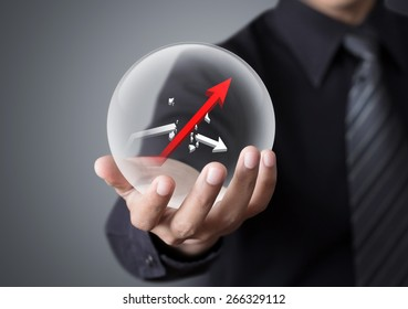 Businessman holds crystal ball with rising red graph and broken white graph