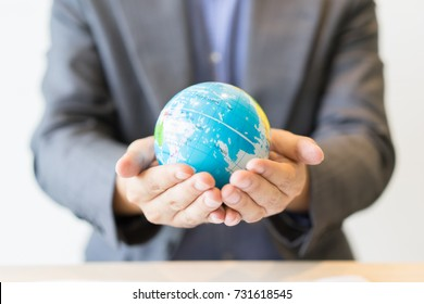Businessman holds Earth in a hand. Business concept selective focus