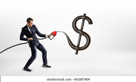 A businessman holds a gas pump nozzle and makes a huge black glossy USD sign on a white background. Oil and gas industry. Commodity exchange. Cost of energy sources.