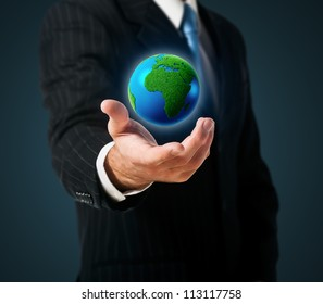 Businessman holds green Earth in a hand