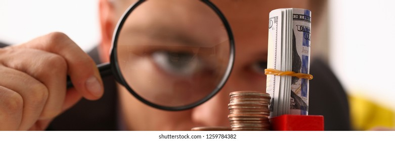 Businessman holds in hand black lens looks with an eye at tower of coins glass portrait closeup. Searches online best schedule 404 page not found concept.