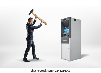 A businessman holds a heavy hammer high over a working bank ATM machine. Getting your money back. Receiving cash. Breaking banking rules.
