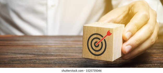 A businessman holds in his hands a wooden block with a target symbol. The concept of achieving business goals. Execution of a business plan. Purposefulness. Goal. Planning. Strategy