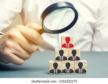 Businessman holds a magnifying glass over the cubes with the image of employees. Staff recruitment. Select a person in the team. Find a talented employee. Bad worker. Weak link. Human Resource.