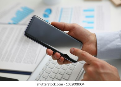 A businessman holds a new smartphone in his hand The mobile application market shows a display you can insert your image for advertising or financial statistics.