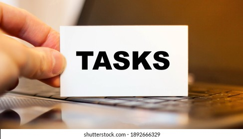 Businessman holds paper with TASKS on the background of a laptop before working day.