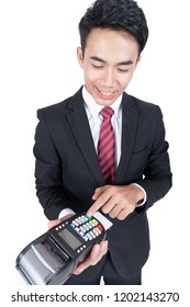 Businessman holds payment terminal in hand.
