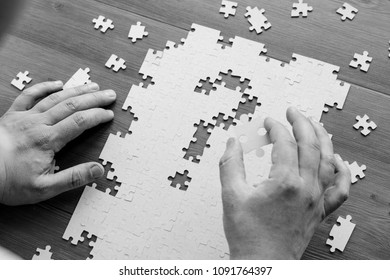 The businessman holds a piece of the puzzle in his hand and reflects on the merger strategy of the corporation. Business and finance. Concepts and implementation of ideas.