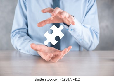Businessman holds a piece of puzzle jigsaw in his hands.The concept of cooperation, teamwork, help and support in business
