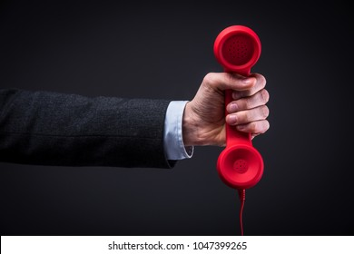 Businessman holds a red telephone with a stretched arm