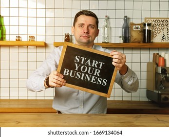 Businessman holds Start your small business sign.