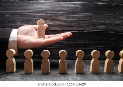 A businessman holds a wooden leader figure on the palm of his hand over a number of other workers. Concept leader, team work. Business and department management. Big boss. Promotion. Career.