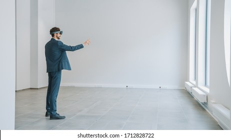 Businessman in Holographic Augmented Reality Glasses Standing in Empty Office and Map it. Sunlight Shines Through Big Windows.
