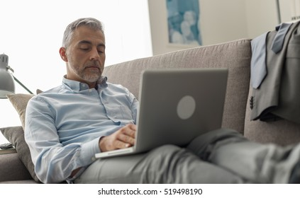 Businessman at home, he is lying down and working from the couch, business and lifestyle concept